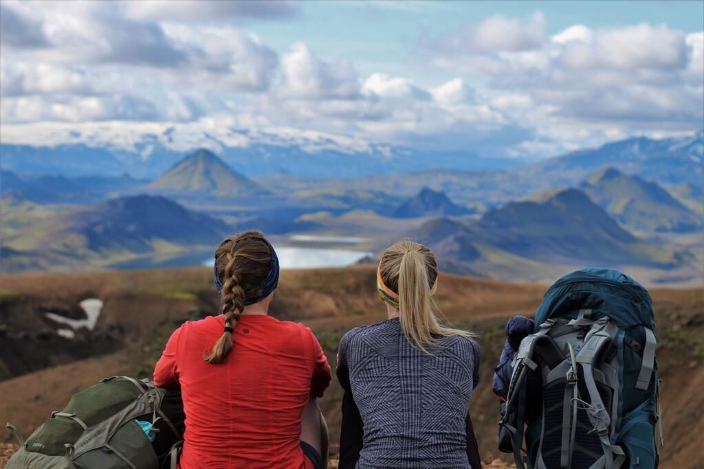 Две девушки с большими рюкзаками отдыхают и смотрят на озеро.