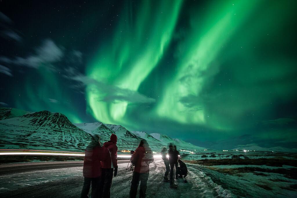 Группа людей наблюдает за северным сиянием.
