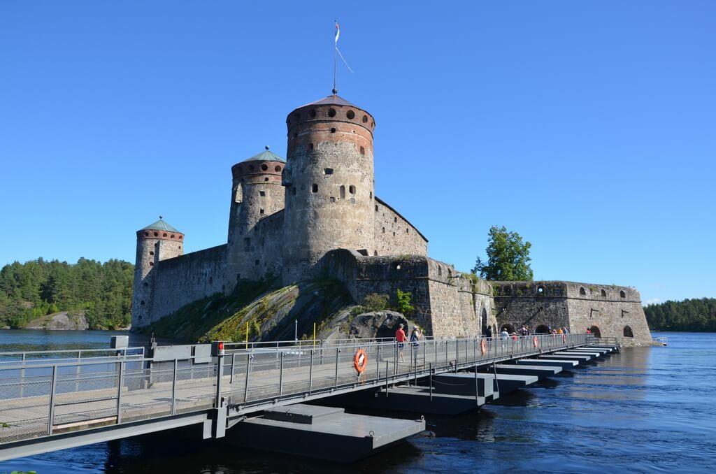 Люди идут по пантонному мосту к каменной крепости с круглыми башнями.