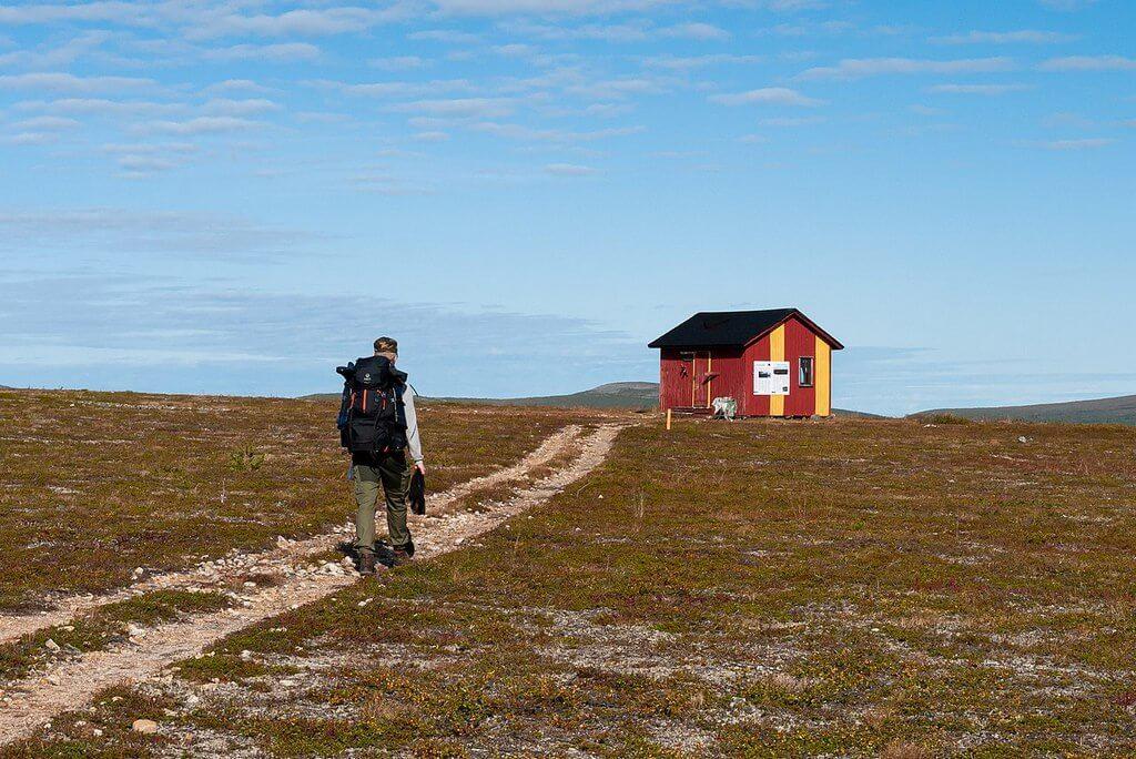 Турист с большим рюкзаком идет по тропинке к маленькому деревянному домику.