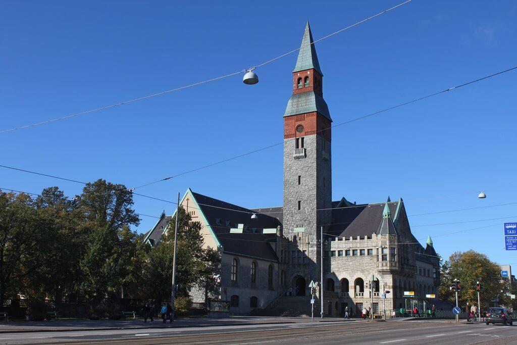 Каменное здание с большой высокой башней по центру.