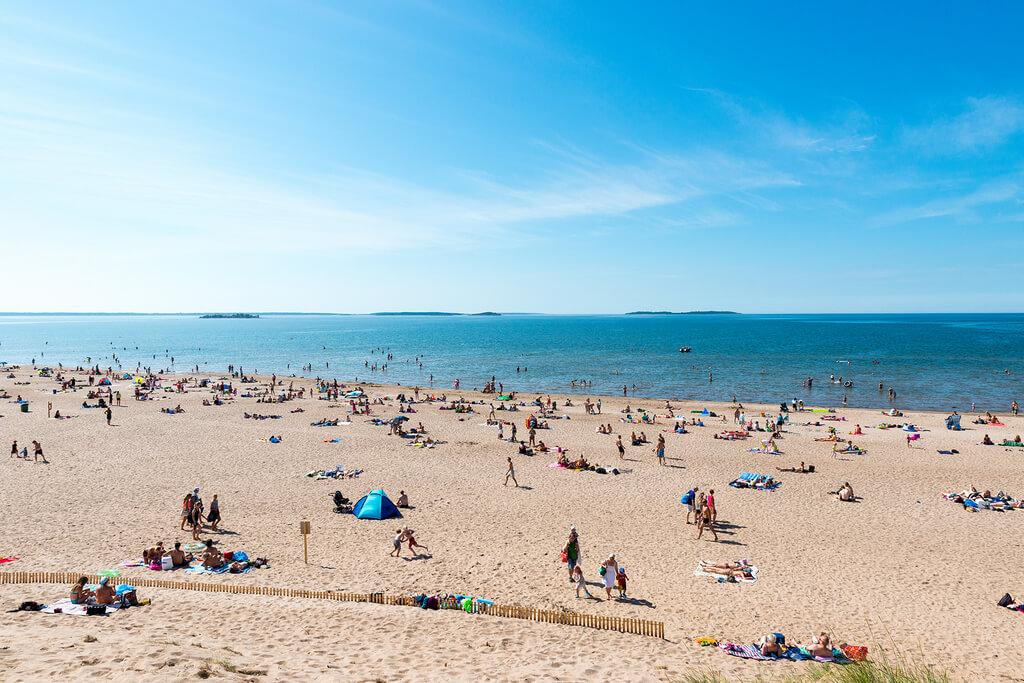 Люди отдыхают на широком пляже в солнечную погоду.
