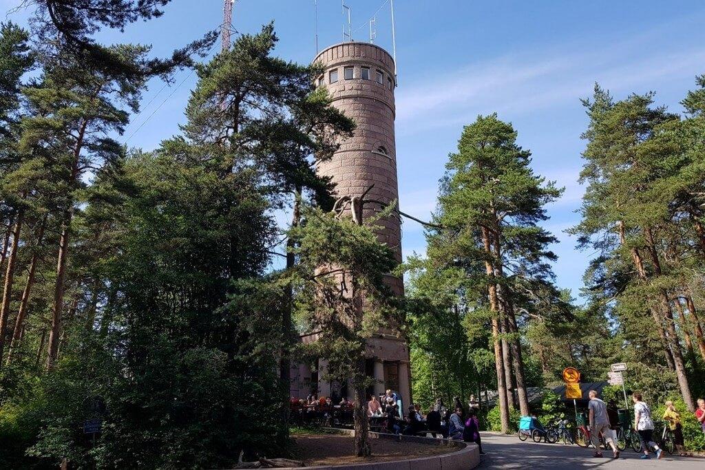 Люди перед входом в круглую башню в лесу.