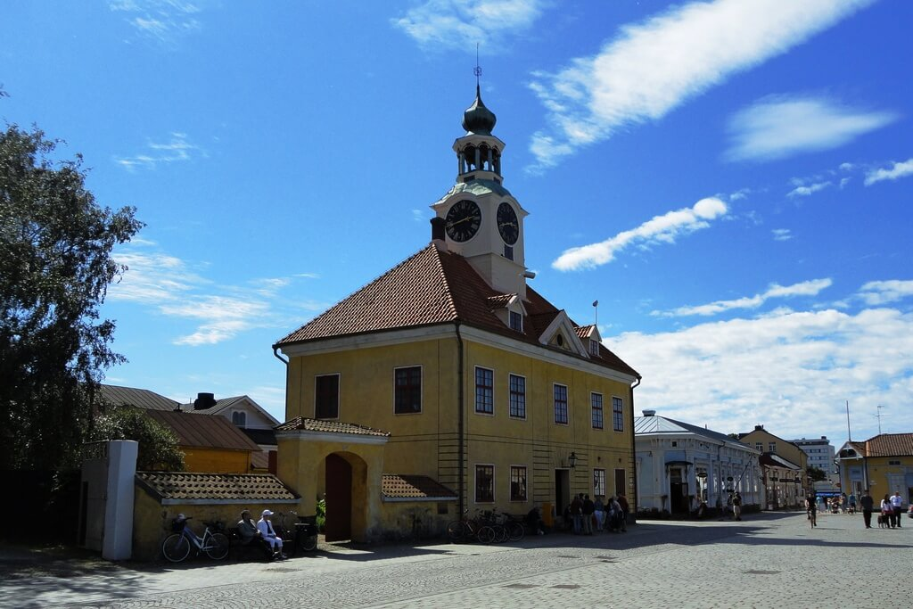 Старинное двухэтажное желтое здание с башней с часами.