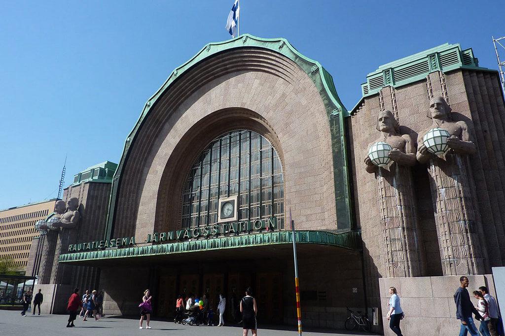 Главный вход в Центральный вокзал Хельсинки, слева и справа от входа — исполины со светильниками.