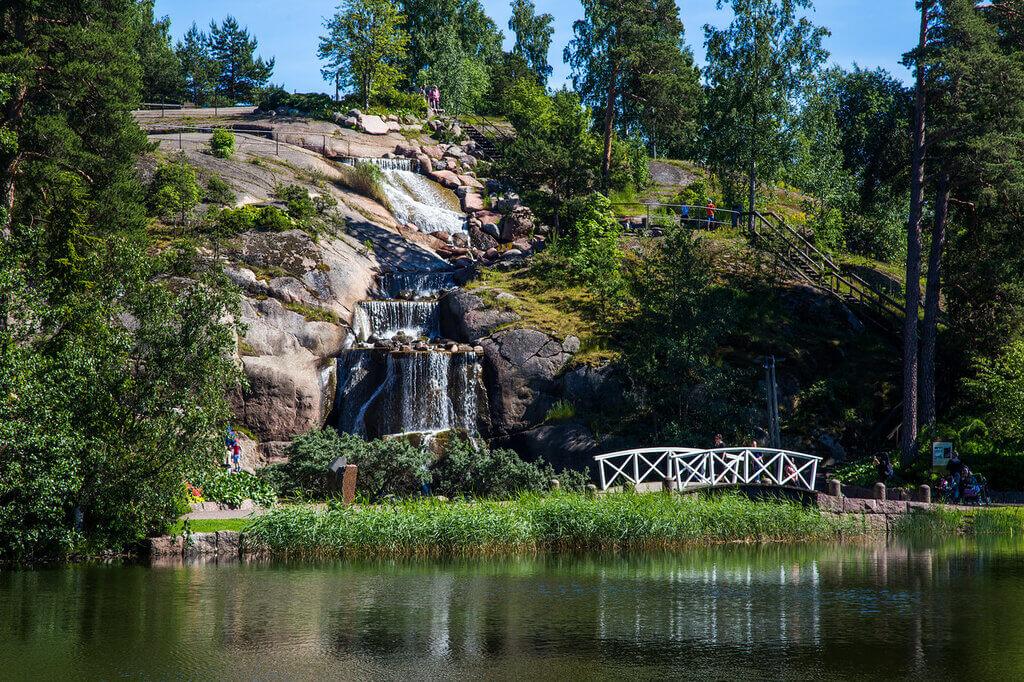 Озеро и мост перед небольшим водопадом.